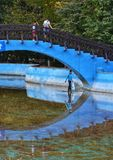 Child walking on water under a bridge. Childs playing on a bridge in the park in summer season stock photo