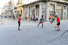 Childs playing football on the street Stock Photography