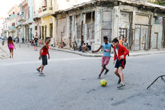 Childs playing football on the street Stock Images
