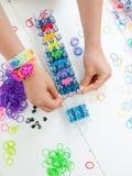 Childs ręki z krosienkiem i multicoloured elastycznymi zespołami Obraz Royalty Free