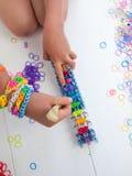 Childs ręki z krosienkiem i multicoloured elastycznymi zespołami Zdjęcia Stock