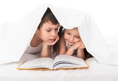 Childs read a book in bed. Children read a book in bed under the blanket Royalty Free Stock Photo
