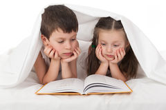 Childs read book in bed under the blanket. Childs read a book in bed under the blanket Stock Images