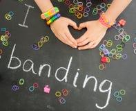 Childs remet former un coeur avec le bracel de bande de métier à tisser Photo libre de droits