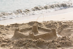 Childs sand castle on beach by ocean Stock Images