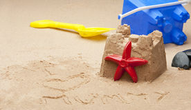 Childs sandcastle on beach. A childs sandcastle on a beach  with the words  I heart mummy in the forground and a oof bucket and spade in the background Stock Photos