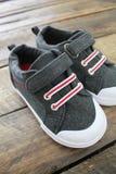 Childs-Schuhe auf einem hölzernen Hintergrund lokalisiert Lizenzfreie Stockfotos