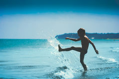 Childs silhouette playing in the sea. Instagram stylisation. Silhouette of young boy who kicks the sea wave on the sandy beach. Instagram stylisation Royalty Free Stock Photos