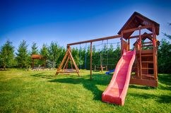Childs slide and swings. Adventure play equipment on green grass with a slide and swings Royalty Free Stock Image