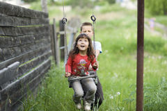 Childs and swing. Big brother swings sister on a swing Stock Photos