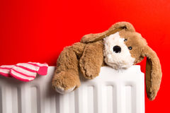 Childs teddy bear and mittens on a bedroom radiator Royalty Free Stock Image