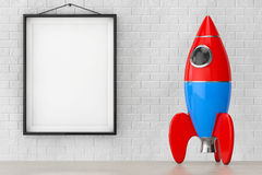 Childs Toy Rocket in front of Brick Wall with Blank Frame. 3d Re Royalty Free Stock Photo