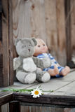 Childs toys left on a country house wooden porch. Childs toys - a teddy bear and a doll - left on a country house wooden porch Royalty Free Stock Photography