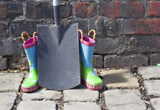 Childs wellington boots. Child's wellington boots and shovel against an old brick wall Stock Images