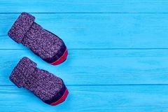 Childs wool socks, copy space. Kids purple woolen knitted socks on blue wooden background. Natural knitted woolen socks for children. Room slippers with Royalty Free Stock Photo