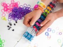 Childs wręcza robić multicoloured elastycznego zespołu bransoletce na b Fotografia Royalty Free