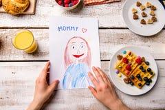Childs-Zeichnung ihrer Mutter Sohn gibt der Mama eine Blume Frühstücksmahlzeit Stockfotos