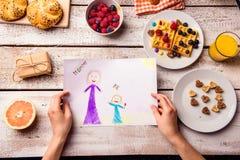 Childs-Zeichnung ihrer Mutter Sohn gibt der Mama eine Blume Frühstücksmahlzeit Stockbilder