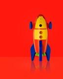 Childsstuk speelgoed raket op rode achtergrond Royalty-vrije Stock Afbeeldingen