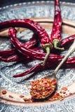 Chile Chili Peppers Varias pimientas de chiles secadas y las pimientas machacadas en una cuchara vieja se derramaron alrededor In Fotos de archivo