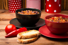 Chile con carne served in the red and black bowls on the wooden background. Chile con carne served in the red and black bowls on the brown wooden background Royalty Free Stock Photo