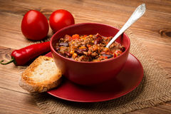 Chile con carne served in the red bowl on the wooden background. Chile con carne served in the red bowl on the wooden brown  background Royalty Free Stock Photography