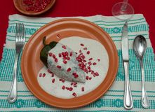 Chile en Nogada is a traditional mexican dish. Poblano pepper st. Uffed with ground meat, covered in walnut cream and pomgrenade seeds royalty free stock images