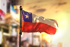 Chile flagga mot suddig bakgrund för stad på soluppgångpanelljuset Royaltyfria Foton