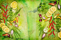 Chile fresco, cebolla, limón e hierbas aromáticas diversos para cocinar en fondo rústico verde imagenes de archivo