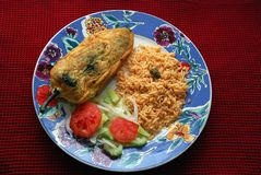 Chile Relleno. Is a Mexican dish which is a Poblano pepper stuffed with cheese or meat fried with a batter of egg. The dish may be served with some Mexican rice stock photo