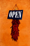 Chile Ristra Open Sign. A dried string of chiles known as a Ristra hangs with an open sign on an adobe wall photographed in Taos, New Mexico Stock Images