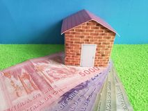 Chilean banknotes, figure of a house on green surface and blue background. Backdrop for mortgage and housing value ads, loan for home construction and remodeling stock photo