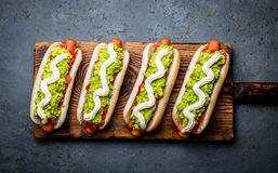 Chilean Completo Italiano. Hot dog sandwiches with tomato, avocado and mayonnaise on wooden board. Top view. Royalty Free Stock Photo