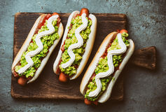 Chilean Completo Italiano. Hot dog sandwiches with tomato, avocado and mayonnaise on wooden board. Top view. Stock Photos