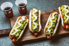 Chilean Completo Italiano. Hot dog sandwiches with tomato, avocado and mayonnaise served on wooden board with drink in Stock Photography