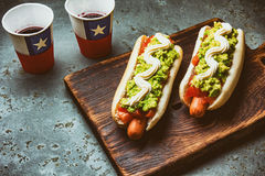 Chilean Completo Italiano. Hot dog sandwiches with tomato, avocado and mayonnaise served on wooden board with drink in Royalty Free Stock Photography