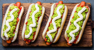 Chilean Completo Italiano. Hot dog sandwiches with tomato, avocado and mayonnaise on wooden board. Top view. Royalty Free Stock Photos