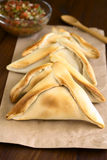 Chilean Empanada. A baked pastry stuffed with meat, with Chilean pebre condiment in the back, photographed with natural light (Selective Focus, Focus on the Royalty Free Stock Photography