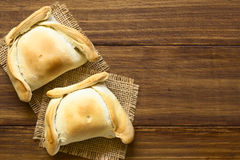 Chilean Empanada. A baked pastry stuffed with meat, photographed overhead on dark wood with natural light Royalty Free Stock Photo