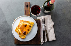 Chilean empanada served on wite plate with red wine. Top view Stock Photos