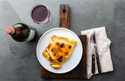 Chilean empanada served on wite plate with red wine. Top view Royalty Free Stock Photos