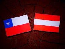 Chilean flag with Austrian flag on a tree stump  Royalty Free Stock Photos