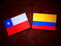 Chilean flag with Colombian flag on a tree stump isolated. Chilean flag with Colombian flag on a tree stump Royalty Free Stock Images