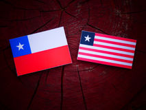Chilean flag with Liberian flag on a tree stump isolated. Chilean flag with Liberian flag on a tree stump Stock Photo