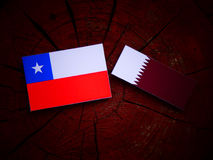 Chilean flag with Qatari flag on a tree stump isolated. Chilean flag with Qatari flag on a tree stump Royalty Free Stock Photography
