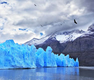 Chilean Patagonia in the clouds. Journey to the End of the World. Chilean Patagonia in the clouds and sunshine. Blue Ice Glacier Gray is reflected in the lake Stock Photos