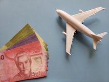 chilenische Banknoten, weißes Plastikflugzeug und blauer Hintergrund lizenzfreie stockfotografie