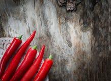 Chiles rojos en fondo de madera envejecido fotos de archivo