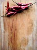 Chiles rojos en la madera Imagenes de archivo