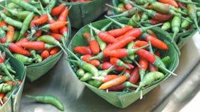 Chiles rojos y verdes en el cuenco que hizo de la hoja del babana Fotos de archivo